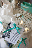 Wedding decoration: cards with a turquoise bow on a bird cage