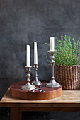 Silver candle holders on a wooden disc and thyme in a basket