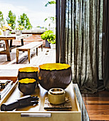 Bowls and decorative hand model on coffee table in front of a linen curtain