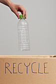 Child's hand placing plastic bottle in cardboard box for recycling