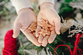 Hands holding small gingerbread cookies
