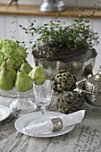 Table decoration with artichokes, pears, wire vine and hydrangea flower