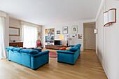 Blaue Polstersofas, Fernsehmöbel und Schaukelstuhl im Wohnzimmer