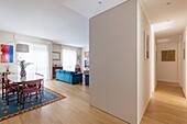 Offener Wohnraum mit Essbereich, blaues Sofa im Hintergrund und Einbauten
