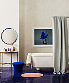 Shower curtain in front of free-standing bathtub in bathroom with blue painted floor