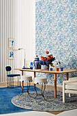 Tisch mit Blumenstrauß und verschiedene Sitzmöbel vor Wand mit blau-weißer Tapete