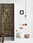 Duschbereich mit Backsteinfliesen, daneben Toilette mit Pendelleuchte