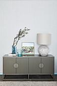 Vase, Bild und Tischlampe auf Sideboard mit geriffelten Türen
