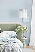 Bett mit gepolstertem Kopfteil, Nachttisch mit Blumenstrauß, darüber Pendelleuchte