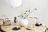 Runder Holztisch mit Vase und asitatischem Gedeck