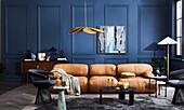Hellbraunes Ledersofa, schwarze Stühle und Coffeetable im Zimmer mit blauer Wand