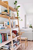 Offenes Bücherregal aus hellem Holz, daneben Stuhl und Sofa in offenem Wohnraum