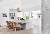 Luxus Küche mit Kücheninsel und Theke aus Marmor, davor Rattansessel