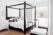 Helles Schlafzimmer mit Balkon, Doppelbett mit schwarz lackiertem Bettgestell