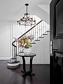 Runder Tisch mit Blumenstrauß und Kronleuchter in eleganter Eingangshalle