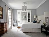 Doppelbett und antike Kommode im Schlafzimmer mit hellgrauen Wänden