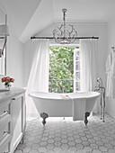 Freistehende Badewanne vor Balkontür