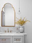 Waschtisch mit Marmorplatte, darüber Goldrahmenspiegel im Badezimmer