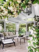 Gemütliche Sitzmöbel auf geräumiger, überadchter Terrasse