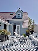 Sonnige Dachterrasse mit Sitzmöbeln, Pflanzentöpfen und Fliesenboden