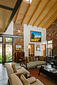 Lounge with double height ceiling, wooden ceiling and natural stone walls