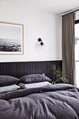 Doppelbett im Schlafzimmer mit schwarz gestrichener Holzverkleidung