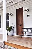 Sitzbank und Pflanzentopf am Eingangstür auf überdachter Veranda