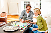 Young couple playing monopoly, Hamburg, Germany