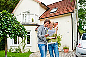 Young couple is looking at documents in front of a house, Hamburg, Germany