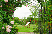 A country garden with a rose arch, and flowering climbing roses.