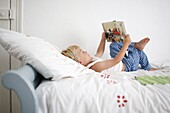 Little boy lying down on his bed reads a book