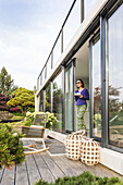 woman at the terrace door with a cup, coodo modern way of living, modern architecture in Hamburg, north Germany, Germany