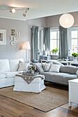 Modernes nordisches Wohnzimmer im Einfamilienhaus mit weiß und grau gewählten Möbeln und Holzfußboden, Korbach, Hessen, Deutschland, Europa