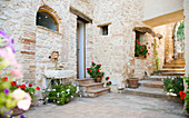 Blumentöpfe entlang der Steinmauer im Innenhof, Spoleto, Italien