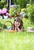 Kleines Mädchen neben Korb mit Möhren im Garten