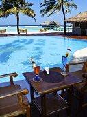 Zwei Cocktails auf Holztisch neben dem Pool mit Blick übers Meer