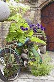 Rusty motorbike by brick wall in garden