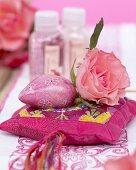 Pink rose on silk cushion, bath products