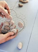 Making a heart with wire and pebbles