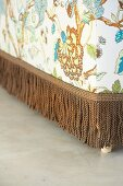 Ottoman upholstered in floral patterned fabric with fringed trim