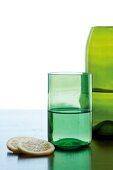 Grünes Glas und grüne Flasche als Vase