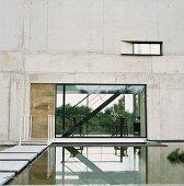 Zeitgenössische Betonarchitektur - Wasserbecken mit Steg und Einblick in offenen Wohnraum mit freistehender Treppe