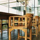 Rustikale Handwerkskunst in zeitgenössischem Gebäude - Holzstühle mit schmiedeeisernen Beschlägen um den alten Esstisch