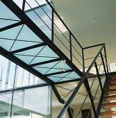 Offene Stahltreppe mit Holzstufen und Steg mit Mattglasboden