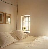 Kleine Fensternische mit innenliegenden Klappläden neben Doppelbett mit frischen, weissen Kissen