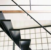 Untersicht schwarzer Treppenstufen aus Stahl mit Geländerstange vor Glasbausteinen