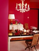 Feminine dining room with pretty chandelier and period furniture surrounded by magenta walls