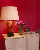 Table lamp with glass base and vase of pink anemones against magenta wall