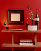 Narrow-necked ceramic vases on wooden shelves below framed drawing on warm red wall