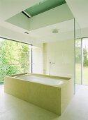 Aufgeglastes Designer-Bad im minimalistischen Stil mit umbauter Wanne und begehbarer Dusche